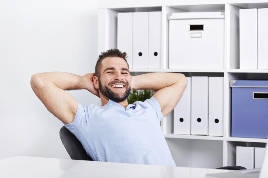 Happy handsome young business man working in the office
